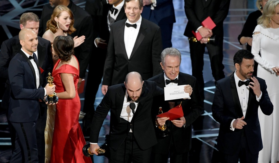 HOLLYWOOD, CA - FEBRUARY 26: (L-R) 'La La Land' producer Jordan Horowitz holds up the winner card reading actual Best Picture winner 'Moonlight' with actor Warren Beatty and host Jimmy Kimmel onstage during the 89th Annual Academy Awards at Hollywood & Highland Center on February 26, 2017 in Hollywood, California. (Photo by Kevin Winter/Getty Images)