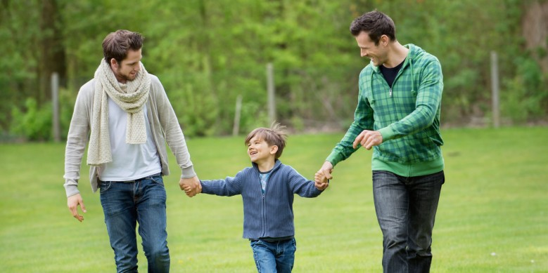 Boy walking with two men in a park. Image shot 2012. Exact date unknown.
