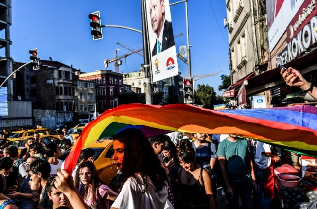 A LGBT rights activist carries a flag in rainbow colors as a banner with a portrait of Turkish President Recep Tayyip Erdogan is seen behind on July 1, 2018 in Istanbul, after Turkish authorities banned the annual Gay Pride Parade for a fourth year in a row. Around 1,000 people gathered on a street near Istiklal Avenue and Taksim Square where organisers wanted to originally hold the parade, an AFP photographer said. Police warned activists to disperse but used rubber bullets against some who tried to access Istiklal Avenue. / AFP PHOTO / BULENT KILIC
