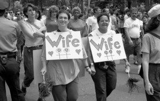 """Duas mulheres com cartazes em que se lê """"Esposa"""" na Marcha do Orgulho a 25 de junho de 1989 em Greenwich Village, em Manhattan, onde se comemorou o 20º aniversário dos motins de Stonewall."""